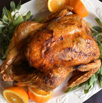 whole cooked turkey on a white platter with oranges and sage
