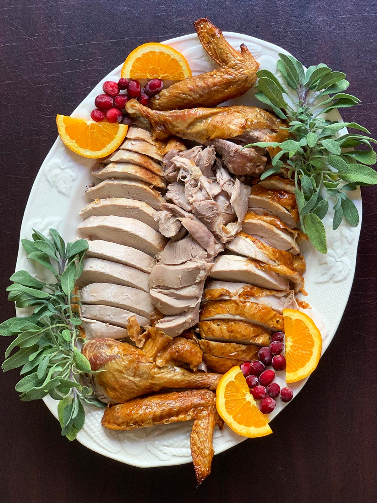 sliced turkey on a white platter with orange, cranberry and sage garnish