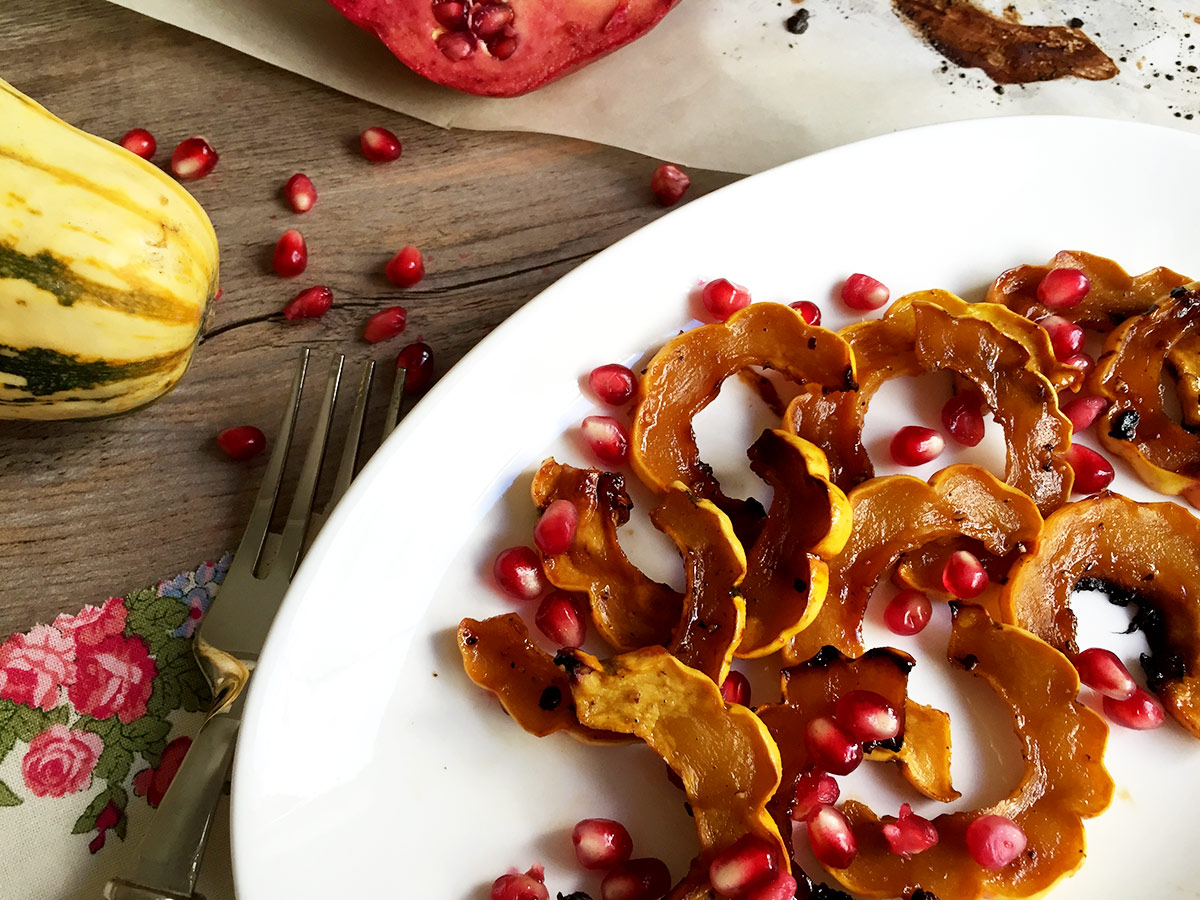 squash out of oven on white plate with pomegranate seeds