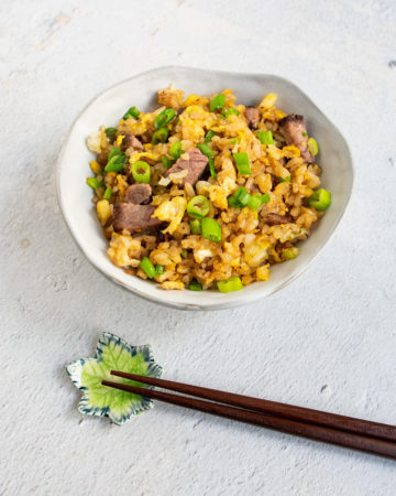 bowl of beef fried rice with wooden chop sticks
