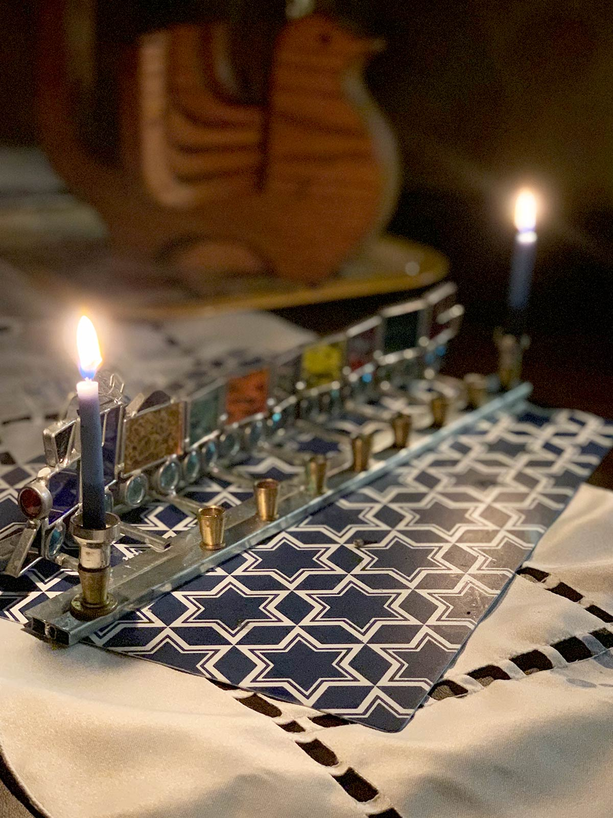 2 hanukkiah with one lit in the foreground