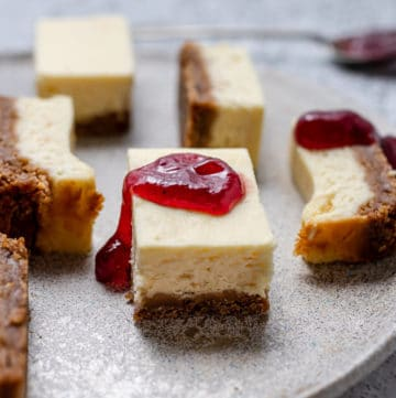 Lemon Cheesecake Bars on a gray plate with jam dripping off of a slice.