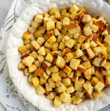 Large white bowl with cornbread and challah bread cubes for stuffing plus fresh herbs and an herb napkin on the side.
