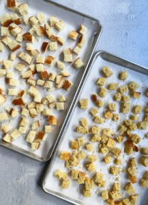 Two trays of unbaked and unseasoned stuffing cubes on parchment paper.