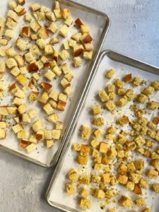 Two sheet trays of bread cubes seasoned and ready to go in the oven.