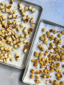 Two trays of baked stuffing cubes at an angle.