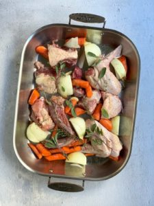 Turkey and vegetables in roasting pan before roasting.