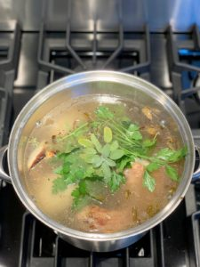 Full stock pot with turkey and vegetables and water and fresh herbs.