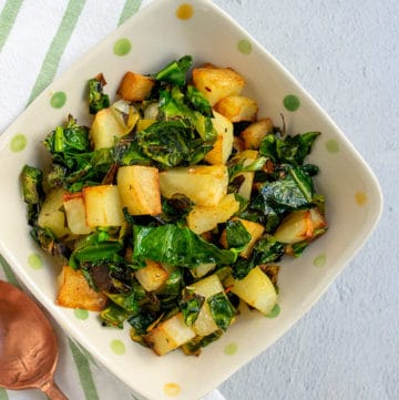 Greens and potatoes in a polka dot bowl with a copper spoon on a striped napkin.